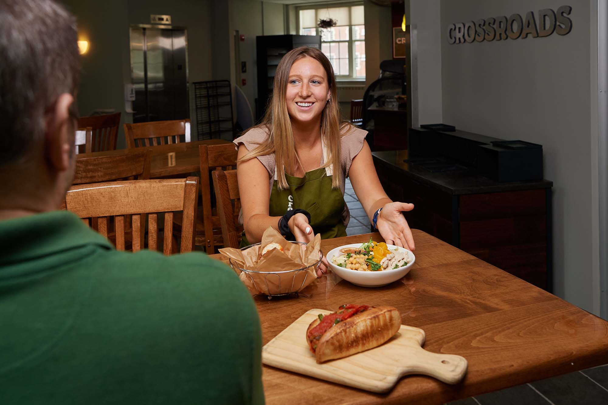 Maddie Pickett gestures to orange faux chicken salad on the table at Crossroads Cafe
