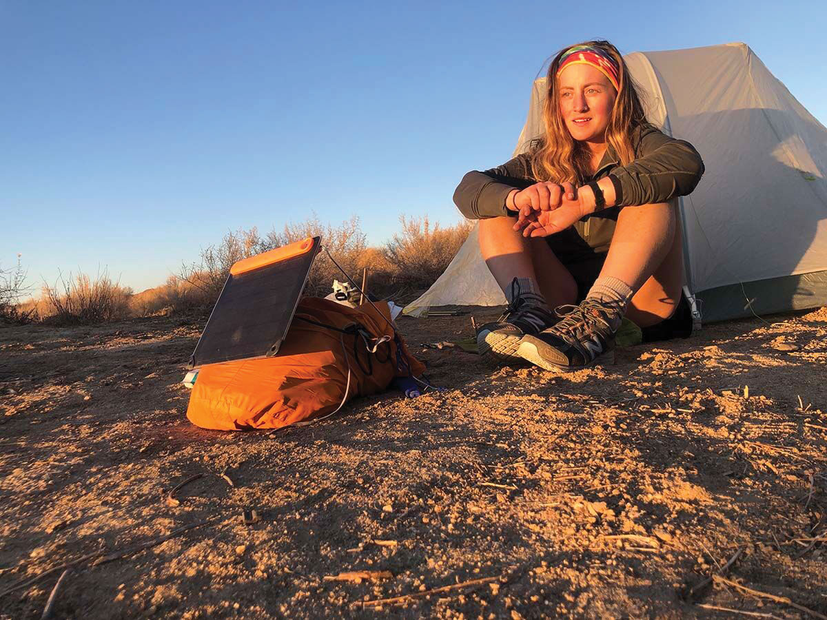 A woman sits outside her tent, basked in sunlight. She has a solar panel hooked up to her backpack to catch the energy.