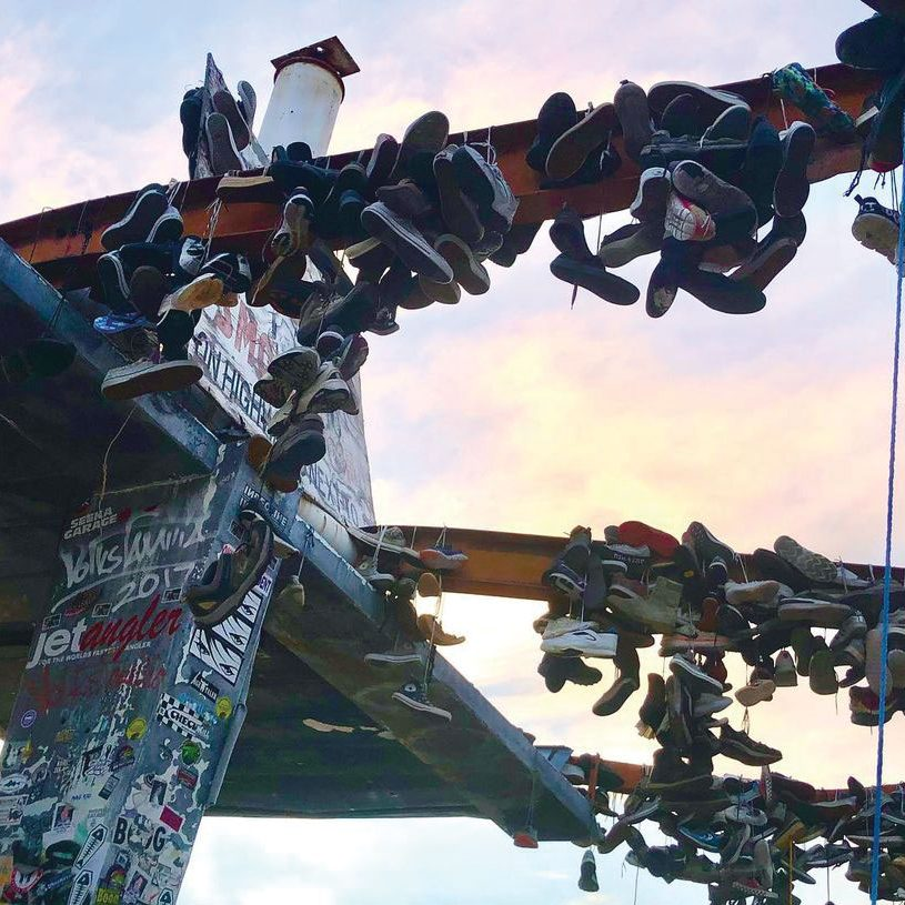 dozens of shoes draped over steel support beams