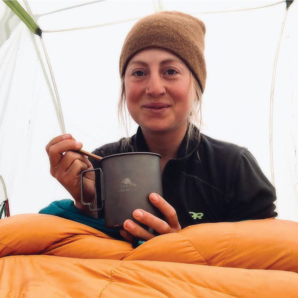 A woman in knit cap is inside a tent, sitting inside a sleeping bag. She holds a mug.