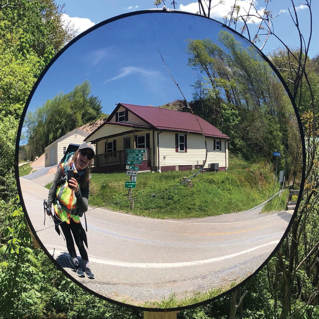 a woman who is backpacking smiles for a selfie at a traffic mirror on a rural suburban street