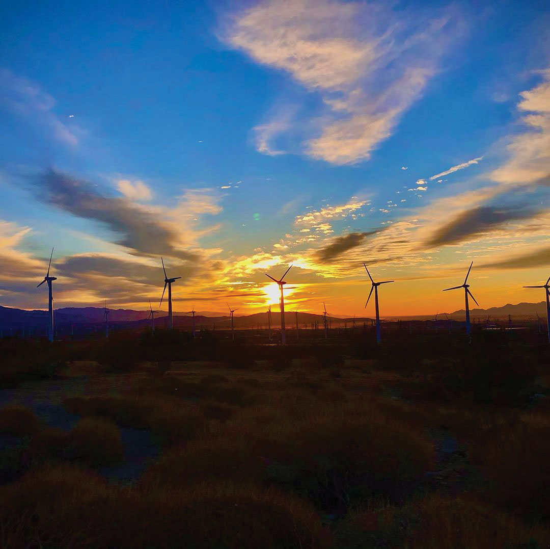 The sun sets behind a desert field of wind turbines