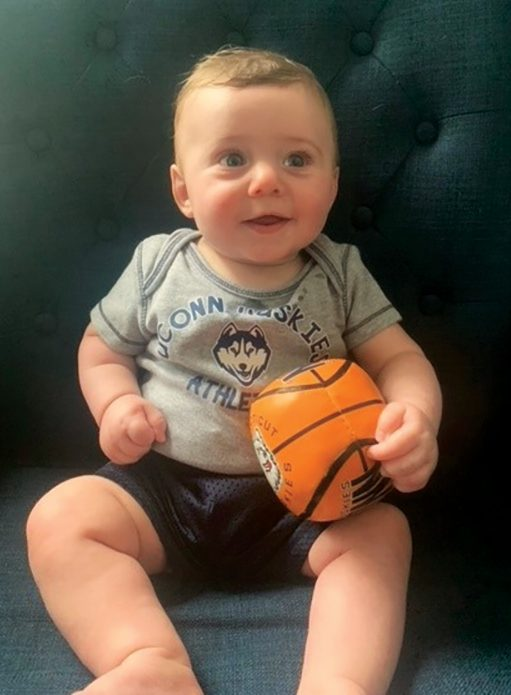 baby holds toy basketball