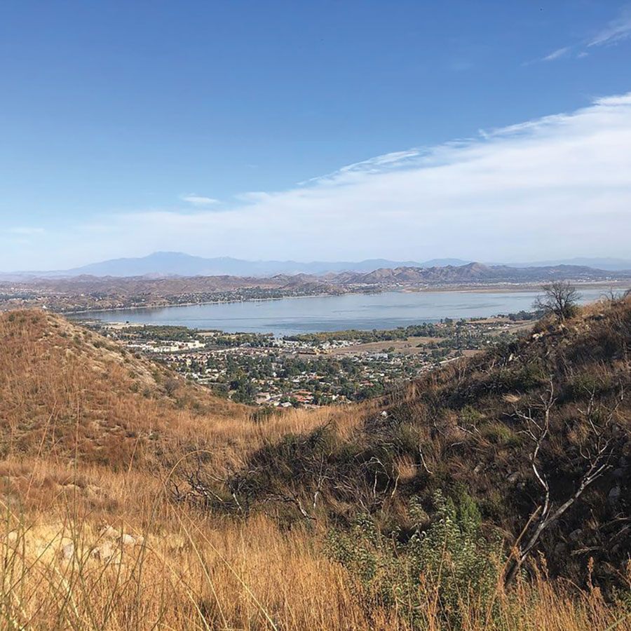 a scenic view of Lake Elsinore, CA, depicting a clear sky, the lake, and mountains in the distance