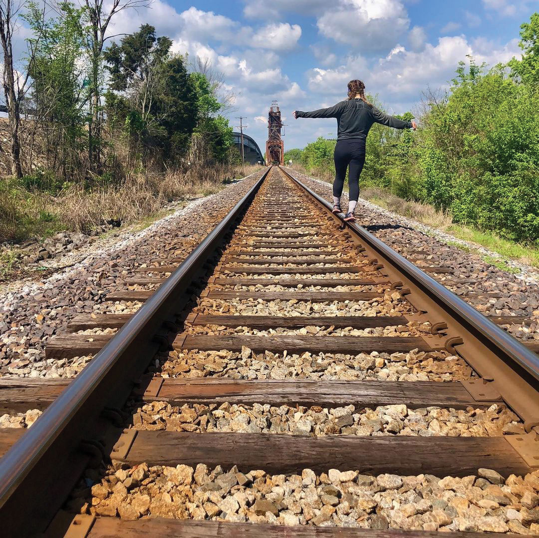 a woman balances on an old railroad track